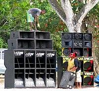 Audio technicians set up massive speaker enclosures for a Jamaican sound  system party.