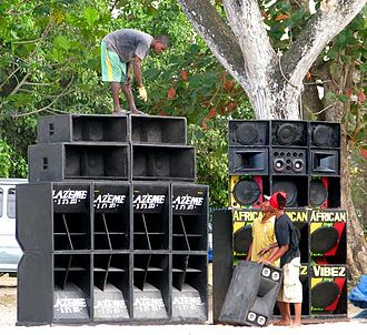 Sound system (DJ) - Audio technicians set up massive speaker enclosures for a Jamaican sound system party.