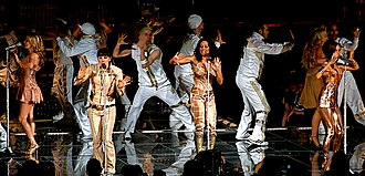Stop (Spice Girls song) - The Spice Girls doing a hand-action dance, while performing the song at the Air Canada Centre in Toronto, Ontario, Canada; during the Return of the Spice Girls tour, dressed in Roberto Cavalli's bronze and copper coloured outfits.