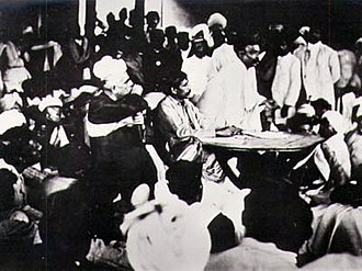"Indian National Congress - Congress ""extremist"" Bal Gangadhar Tilak speaking in 1907 as the Party split into moderates and extremists. Seated at the table is Aurobindo Ghosh and to his right (in the chair) is G. S. Khaparde, both allies of Tilak."