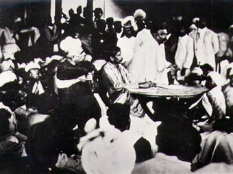 Sri Aurobindo seated at the table, with Tilak speaking: Surat session of Congress, 1907 Sri Aurobindo presiding over a meeting of the Nationalists after the Surat Congress, with Tilak speaking, 1907.jpg