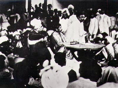 "Congress ""extremist"" Bal Gangadhar Tilak speaking in 1907 as the party split into the Moderates and the Extremists.  Seated at the table is Aurobindo Ghosh and to his right (in the chair) is Lala Lajpat Rai, both allies of Tilak."
