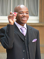 Wiltshire holding his MBE high in his right  hand.  He is shown from the waist up, smiling and formally dressed  (black suit and waistcoate; white shirt with lilac tie, loosely tied).   His head is shaved; a ring is visible on his right little finger