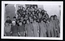 A grouping of about 30 students in front of a brick building. There is a nun in the back row.