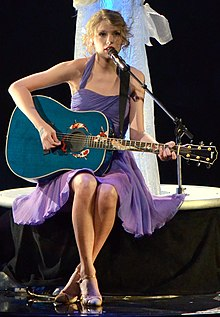 Taylor Swift, wearing a purple dress, plays a blue acoustic guitar ...