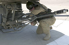 Soldier adjusting big gun hanging from helicopter