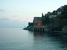 Холм заселен с домами наклонен вниз в сине-зеленое море под каменным доком с пятью арок.  Каменная стена простирается вдоль моря из дока в нижнем правом углу.