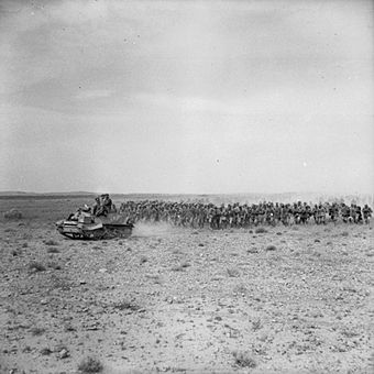 A Universal Carrier escorts a large contingent of Italian prisoners, captured at El Hamma, 28 March 1943 The British Army in Tunisia 1943 NA1630.jpg