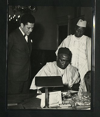 Agent-general - Signing the visitors' book at Nigeria House with Arthur Prest (left) and Alhaji Sa'adu Alanamu (right)