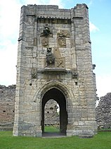 Tall tower with an arched passageway through the bottom. Above the archway are heraldic symbols.