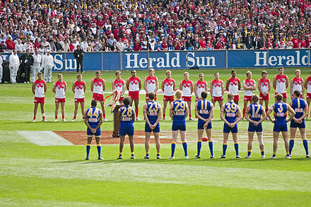 The West Coast Eagles and Sydney Swans line up for the national anthem at the 2005 AFL Grand Final. Traditionally held at the MCG, the Grand Final is the highest attended club championship event in the world. The teams line up for the national anthem, 2005 AFL Grand Final.jpg