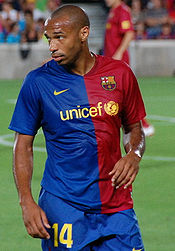 "A dark-skinned man wearing a blue and red shirt and blue shorts with the number ""14"" displayed on the lower right thigh."