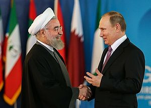 Third GECF summit - Iranian President Hassan Rouhani speaking with Russian President Vladimir Putin before the summit