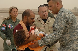 Tuz Khurmatu - An U.S. Army Soldier and a Turkish Air Force member transport an Iraqi child to safety during a multinational humanitarian airlift effort on Kirkuk Air Base, Iraq, July 8, 2007. The victim was hurt in an attack in Tuz Khurmato.