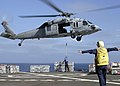 US Navy 040912-N-0000G-001 Aviation Boatswain's Mate 2nd Class Blunt guides a MH-60S Knighthawk to receive ordnance on the flight deck.jpg