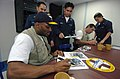 US Navy 050212-N-8629M-129 New York Giants wide receiver Amani Toomer, foreground, and quarterback Kurt Warner sign autographs for Sailors stationed aboard the Military Sealift Command (MSC) hospital ship USNS Mercy (T-AH 19).jpg