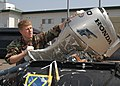 US Navy 050329-N-2385R-024 Electrician's Mate 2nd Class Daniel K. Ryan, assigned to Explosive Ordnance Disposal Mobile Unit Five (EODMU-5), Detachment Five One, washes the engine of a Combat Rubber Raiding Craft.jpg