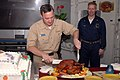 US Navy 061123-N-0237L-016 USS Essex (LHD 2) Commanding Officer, Capt. Brian Donegan, cuts a Thanksgiving turkey on the ship's Mess Decks as Essex' Supply Officer, Cmdr. Carl Weiss looks on.jpg