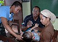 US Navy 070602-N-2296G-075 Philippines Navy Hospitalman 3rd Class Norman Sanico, together with Lt. j. g. Melvin Pruitt with Navy reserve Operational Health Support Unit, Det J, examine a young resident of the area during the Me.jpg
