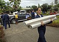 US Navy 070808-N-4954I-008 Cryptographic Technician (Technical) Seaman Sarah Curl carries rolls of plastic sheeting in preparation for a community relations project at Modilon General Hospital in support of Pacific Partnership.jpg