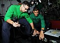 US Navy 080627-N-9898L-020 Aircrew Survival Equipmentman 2nd Class Joe Quintero, left, and Aircrew Survival Equipmentman 1st Class Brian Hawks fill emergency breathing bottles for survival vests.jpg