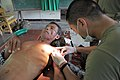 US Navy 090420-A-0759M-052 Hospital Corpsman 3rd Class Justin Azucenas, stitches the wound of a local man at Umiray Elementary School during a medical civic action project supporting Balikatan 2009.jpg