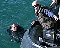US Navy 090716-N-3581D-153 U.S. Navy Diver 1st Class Anthony Carter, left, assigned to Explosive Ordnance Disposal (EOD) Unit 1, holds on to a rigid hull inflatable boat after a dive while listening to Navy Diver 1st class Mich.jpg
