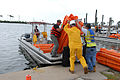 US Navy 100430-N-6268N-041 Contract employees with BP America, Inc. load an oil containment boom onto a work boat at Naval Air Station Pensacola to assist in oil recovery efforts from the Deepwater Horizon oil spill in the Gulf.jpg
