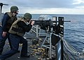 US Navy 110619-N-NL541-329 Midshipmen 2nd Class Alex Nestle fires a .50-caliber machine gun aboard the guided-missile frigate USS Thach (FFG 43).jpg