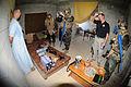 US Navy 110831-N-UH337-111 Lt. Bryan K. Wilson photographs Builder 2nd Class Brandon D. Morgan, simulating an insurgent, and a table of evidence as.jpg