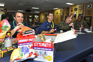US Navy 111231-N-KS651-383 Cmdr. Homer Denius, Lt. Col. Andrew Bergen, and members of the wardroom celebrate New Year's Eve by playing bingo in the.jpg