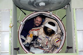 Yury Usachov - Usachov moves an Orlan spacesuit through the forward hatch of the Zvezda Service Module.