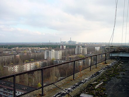 A photograph taken in the abandoned city of Pripyat. The Chernobyl nuclear power plant can be seen on the horizon. View of Chernobyl taken from Pripyat.JPG
