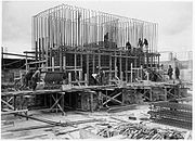Scaffolding surrounds a half finished concrete foundation. Dozens of metal steel poles rise from the foundation. A dozen workmen are visible and involved in various construction tasks.