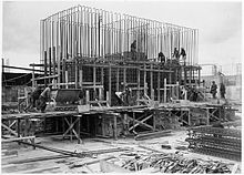 Scaffolding surrounds a half-finished concrete foundation. Dozens of metal steel poles rise from the foundation. A dozen workmen are visible and involved in various construction tasks.