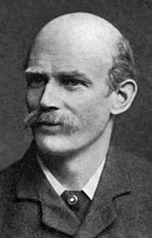 A man in his forties, balding and with a mustache, wearing a dark suit and a tie