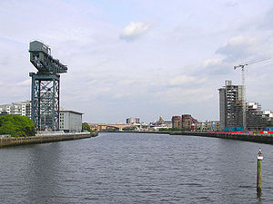 The Clyde flowing through Glasgow. The Finnieston Crane on the left is seen as a lasting symbol of the industrial heritage of the Clyde.