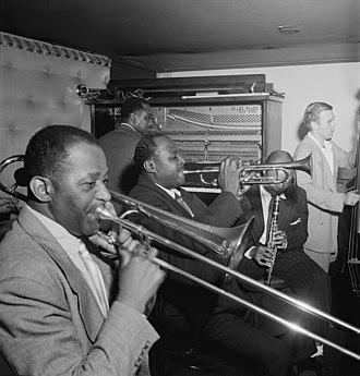 Sammy Price - Price (background) with Wilbur De Paris (left), Sidney De Paris, Eddie Barefield and Charlie Traeger, Jimmy Ryan's (Club), New York, c. July 1947. Photograph by William P. Gottlieb.
