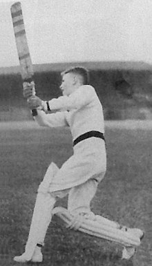 A male youth wearing cricket pads, gloves, white uniform and sweater, stands on the grass and follow through after swinging his bat in a vertical arc.