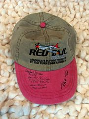 a gray baseball cap with light red brim. The cap has a Red Tail Project logo and the brim has several autographs.