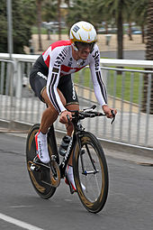A cyclist wearing a skinsuit and riding an aerodynamic bike.
