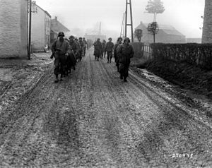 28th Infantry Division (United States) - Men of the 28th Infantry Division march down a street in Bastogne, Belgium, December 1944. Some of these men lost their weapons during the German advance in this area.