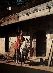A man sits on his horse in the street of the old city of Gwalior by Jules Gervais-Courtellemont.jpg