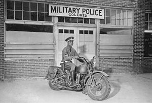"""Racism against African Americans in the U.S. military - An African-American military policeman on a motorcycle in front of the """"colored"""" MP entrance, Columbus, Georgia, in 1942."""