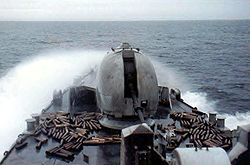 A large cannon on the front of a warship surrounded by empty shells; waves are breaking over the ship.