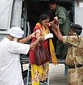 An injured pilgrim is helped to get down from a chopper, at Gauchar, Uttarakhand.jpg