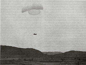 A dark shape is suspended in the air beneath three parachutes, while hills rise in the foreground