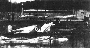 Three-quarter rear view of biplane on floats, taxiing along a stretch of water towards shore