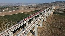 רכבת חשמלית חולפת על גשר הרכבת מעל עמק איילון