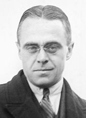 Black and white photo of a bespectacled man in suit and tie looking at the camera